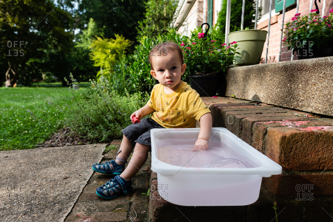 Small child with hand in water on front stoop