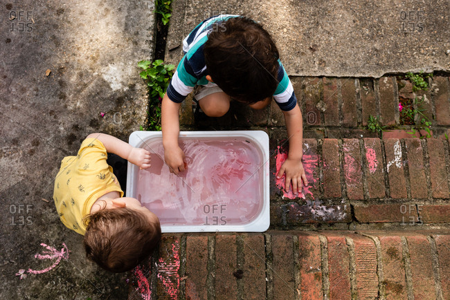 Little boys patting messy wet chalk on porch stairs