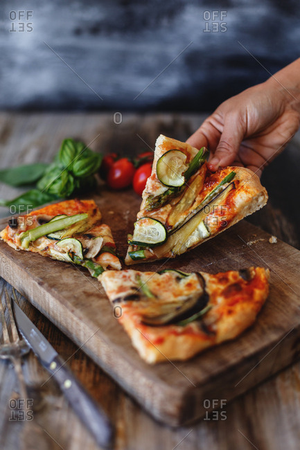 Hand holding a slice of veggie pizza