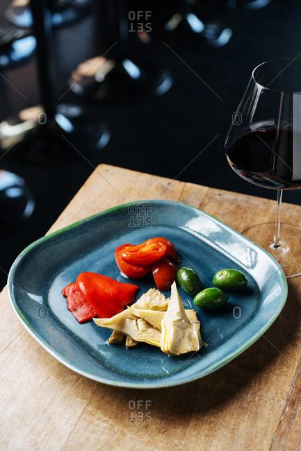 Veggies on a plate beside wine