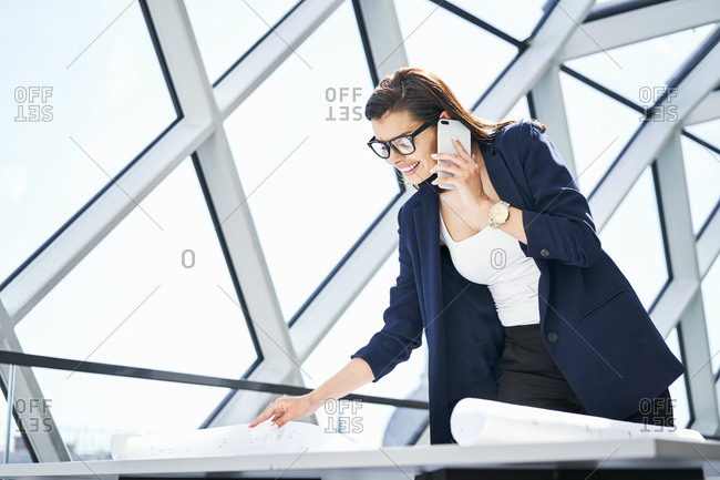 Smiling businesswoman on cell phone looking at plan in office