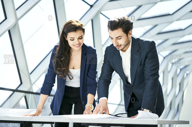 Smiling businesswoman and businessman looking at plan in office