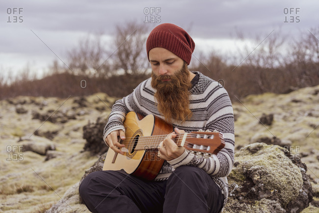 Man sitting in wilderness- playing the guitar