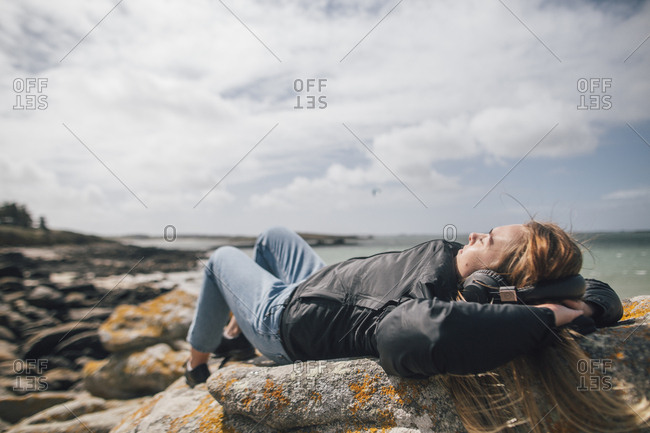 France- Brittany- Landeda- young woman wearing headphones lying at the coast