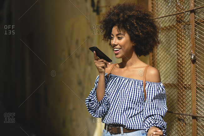 Portrait of fashionable young woman with curly hair on the phone
