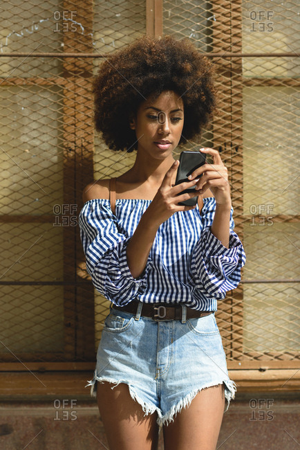 Portrait of fashionable young woman with curly hair looking at smartphone