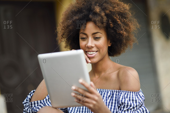 Portrait of smiling young woman with curly brown hair using tablet