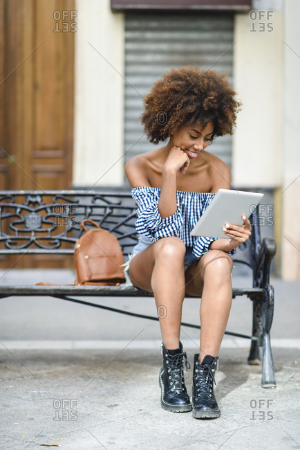 Young woman sitting on bench in the city using tablet