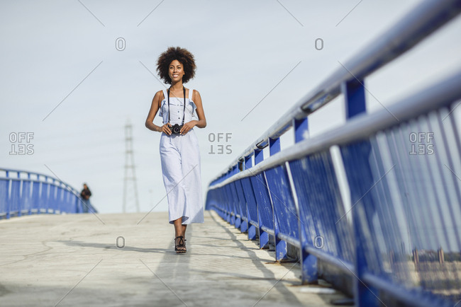 Content young woman with camera walking on a bridge