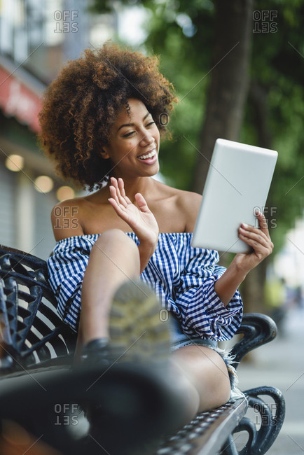 Smiling young woman sitting on bench with tablet having video chat