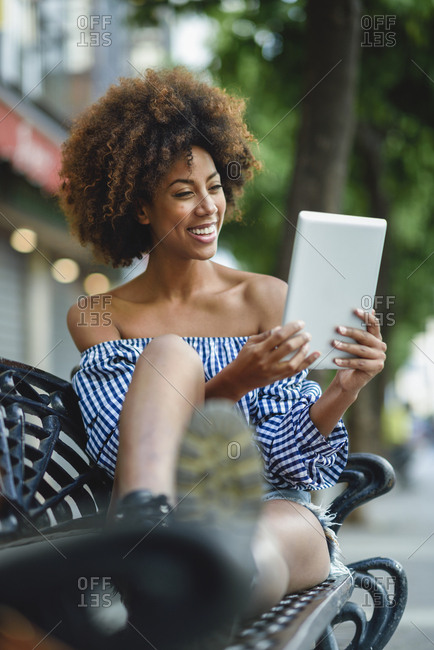 Portrait of laughing young woman sitting on bench using tablet