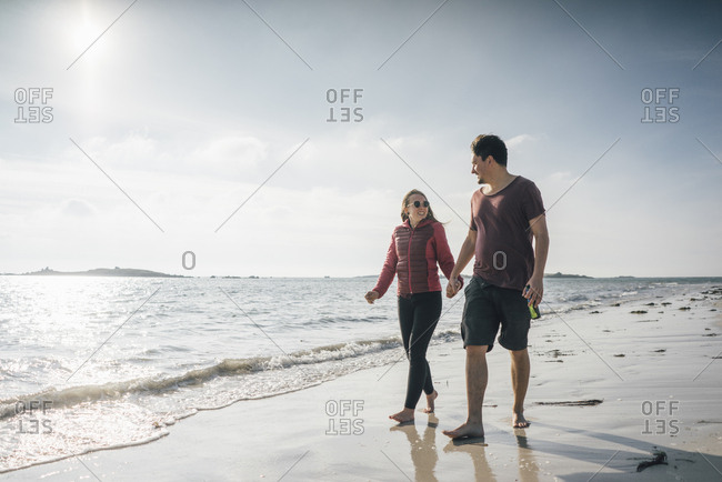 France- Brittany- Landeda- couple walking hand in hand on the beach