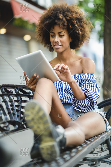 Portrait of young woman with curly hair sitting on bench using tablet