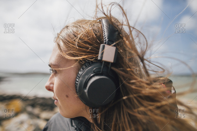 France- Brittany- Landeda- woman wearing headphones at the coast