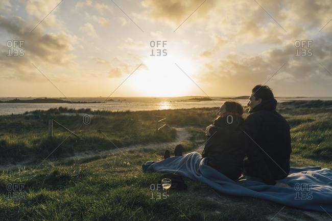 France- Brittany- Landeda- couple sitting  at the coast at sunset