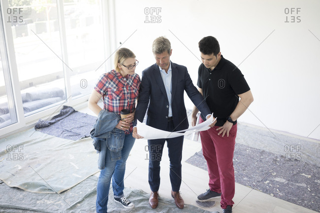 Man in suit and couple looking at blueprint in unfinished  building