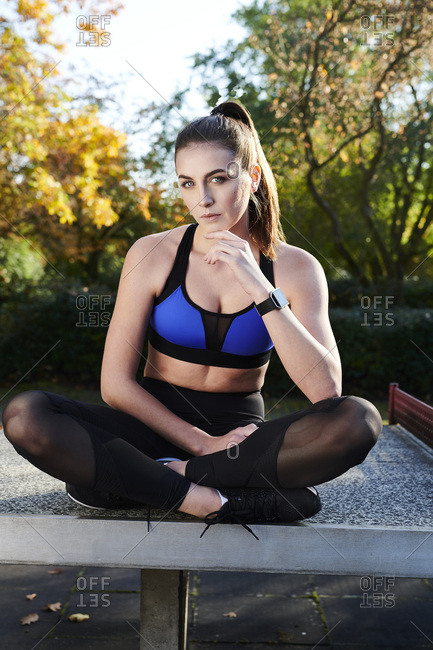 Sportive woman sitting on table tennis table