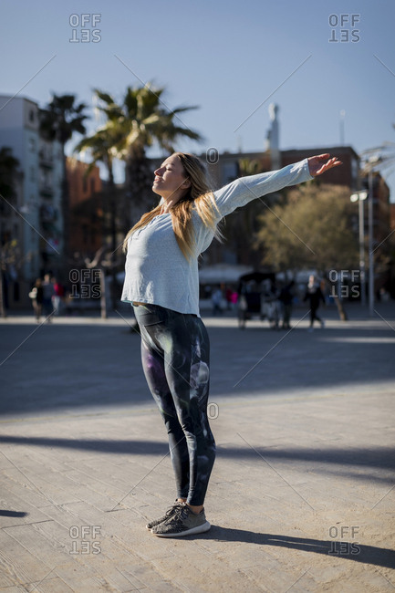 Spain- Barcelona- woman stretching on beach promenade