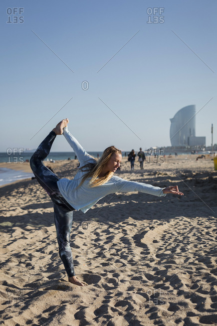 Woman doing yoga on the beach- dancer position