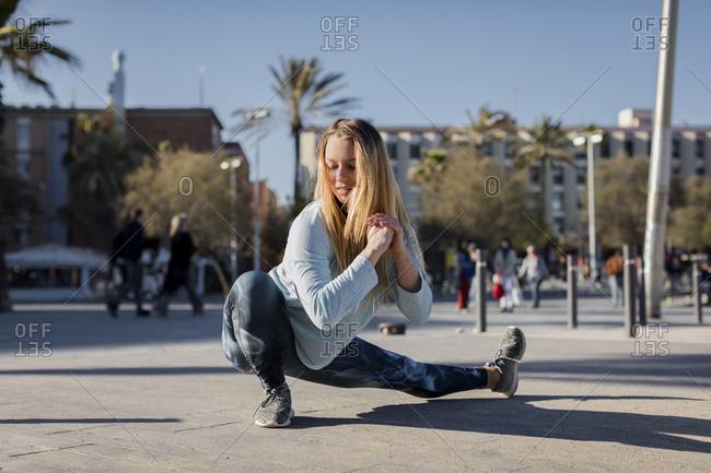 Spain- Barcelona- woman stretching leg on beach promenade