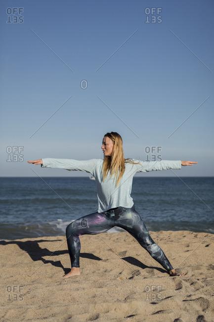 Woman doing yoga on the beach- warrior pose