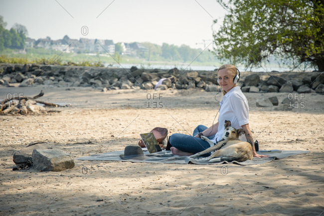 Smiling woman sitting on blanket at a river with dog wearing headphones