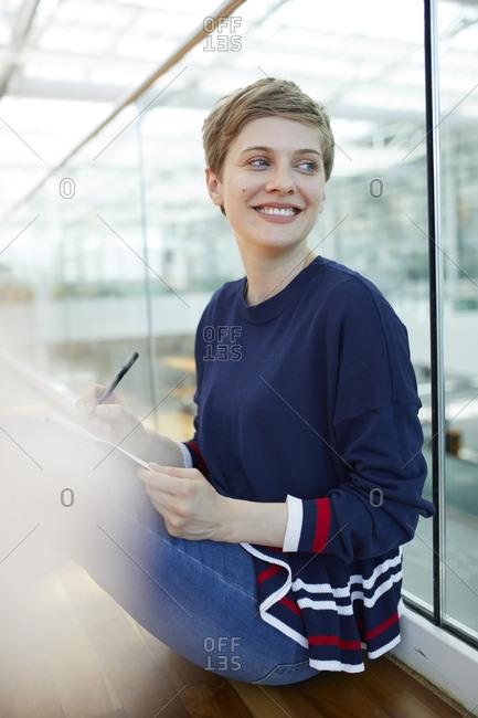 Blond businesswoman sitting on ground- writing in notebook