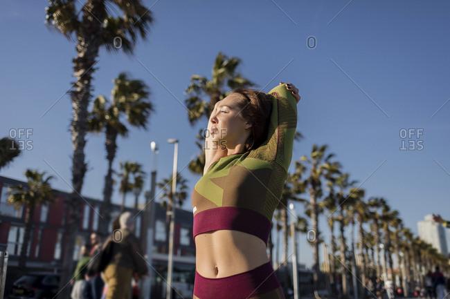 Sporty woman stretching arm