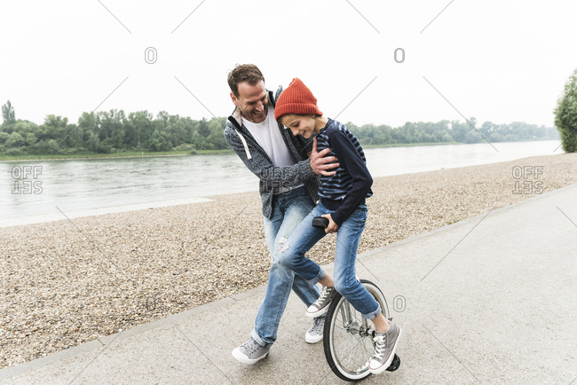 Happy father supporting son on unicycle at the riverside