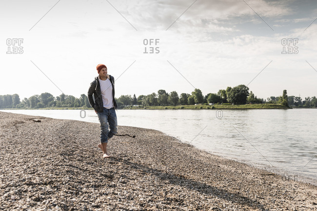 Mature man with red beanie walking at Rhine riverbank