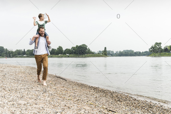 Happy father carrying son on shoulders at the riverside
