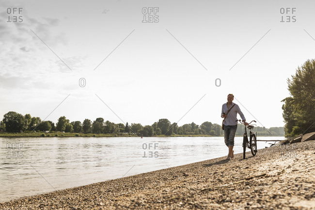 Mature man with bike using smartphone at Rhine riverbank