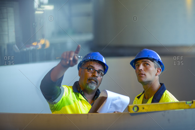 Engineers in industrial plant discussing work