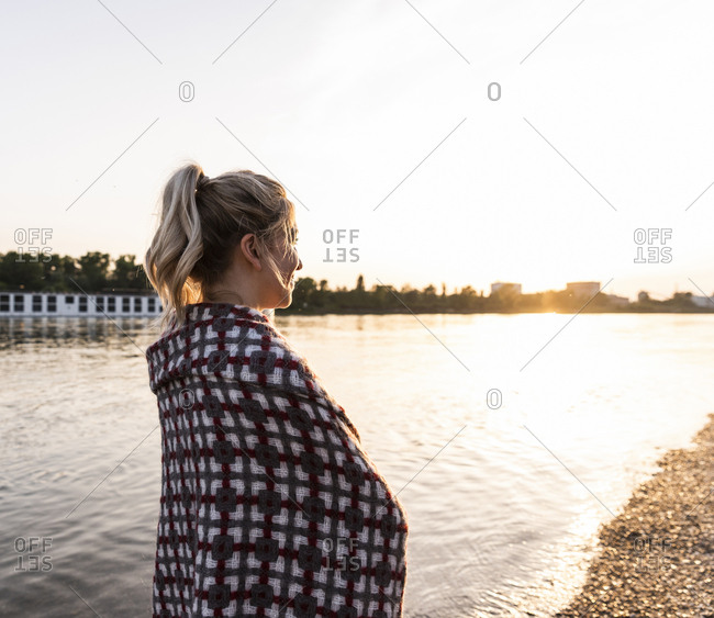 Blond woman at riverside in the evening- wrapped in a blanket