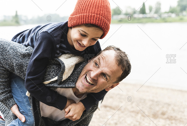 Happy father carrying son on piggyback at the riverside