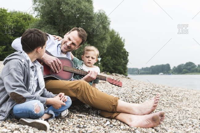 Happy father with two sons sitting at the riverside playing guitar