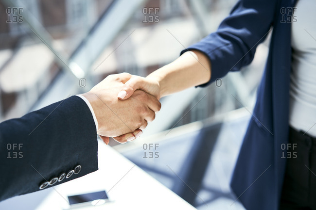 Close-up of handshake of businesswoman and businessman