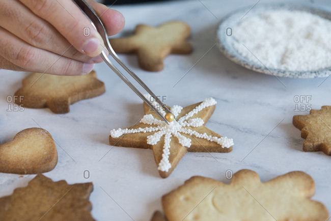 Man's hand decorating Christmas cookie- close-up