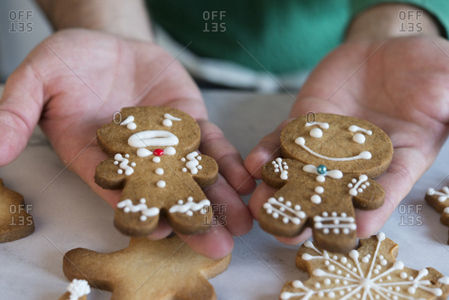 Man's hands holding two different Gingerbread Men- close-up