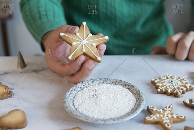 Man's hand holding Christmas Cookie- close-up