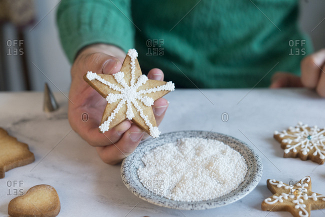 Man's hand holding homemade Christmas Cookie- close-up