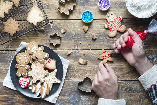 Man's hand decorating Christmas cookie