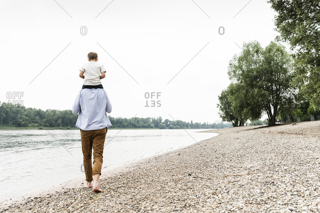 Father carrying son on shoulders at the riverside