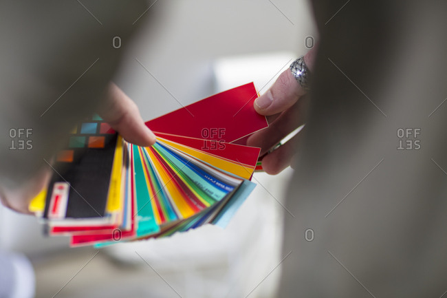 Close-up of man holding color swatches in office