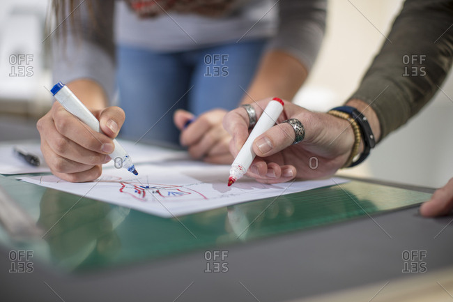 Close-up of two colleagues drawing at desk in office stock