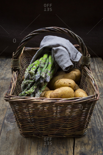 Organic green asparagus and organic potatoes in wickerbasket