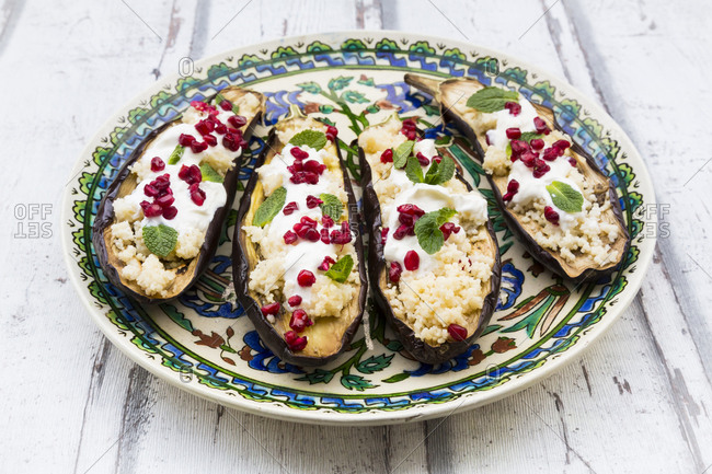 Filled aubergines with couscous- yogurt sauce- mint and pomegranate seeds