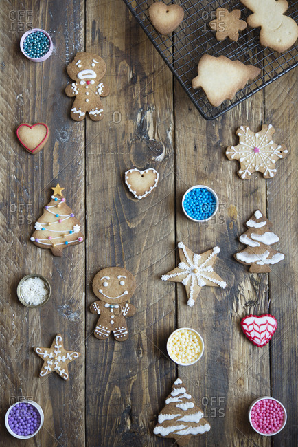 Decorated and unfinished gingerbread cookies on wood