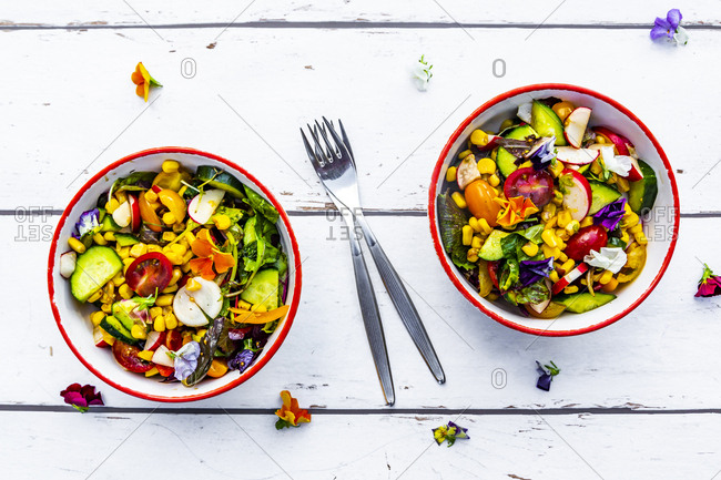 Two bowls of mixed salad with edible flowers