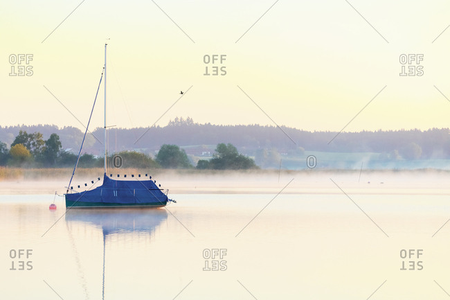 Germany- Bavaria- Chiemsee- covered sailing boat in the evening light